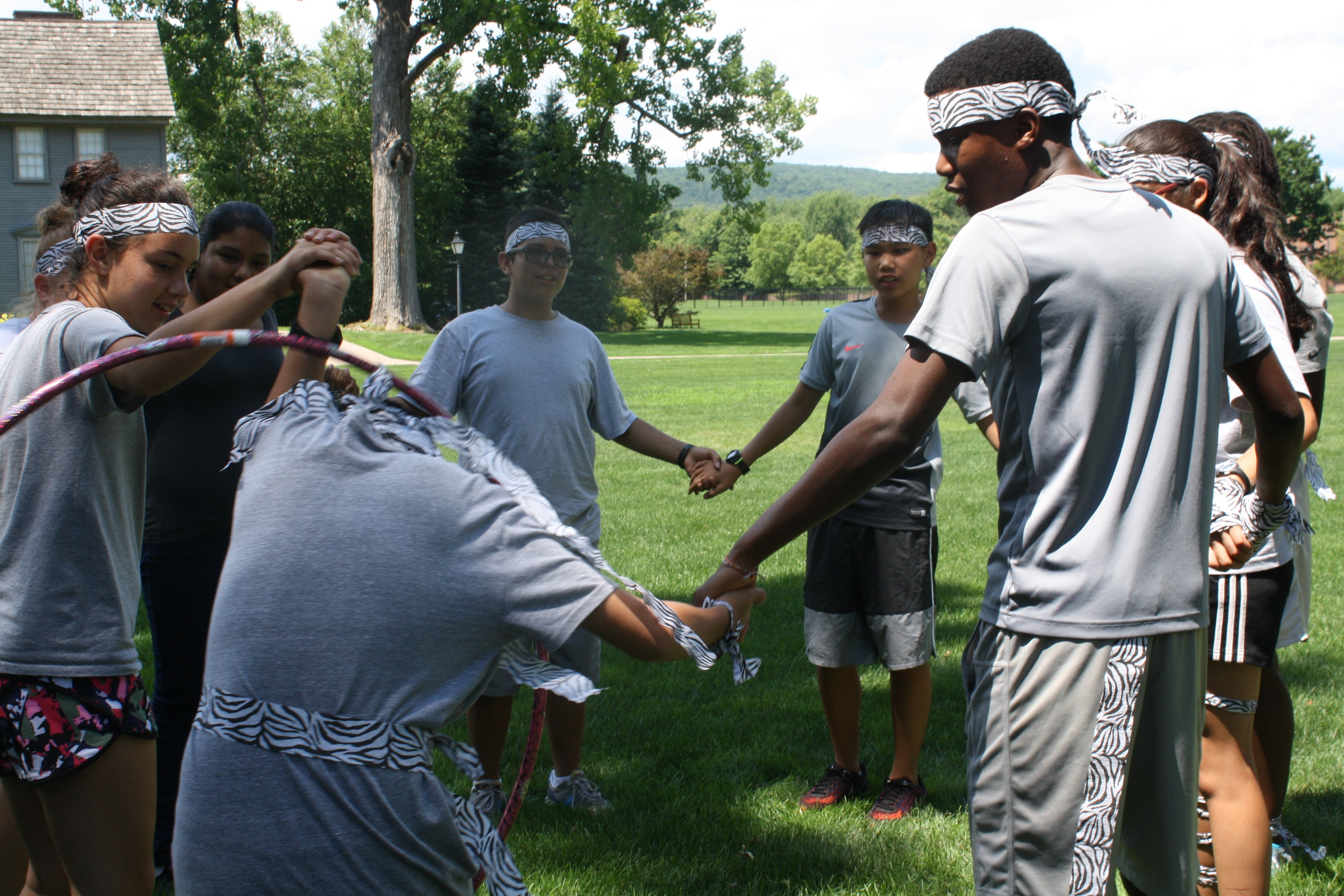 Midde school students laugh as they struggle to complete summer field games.