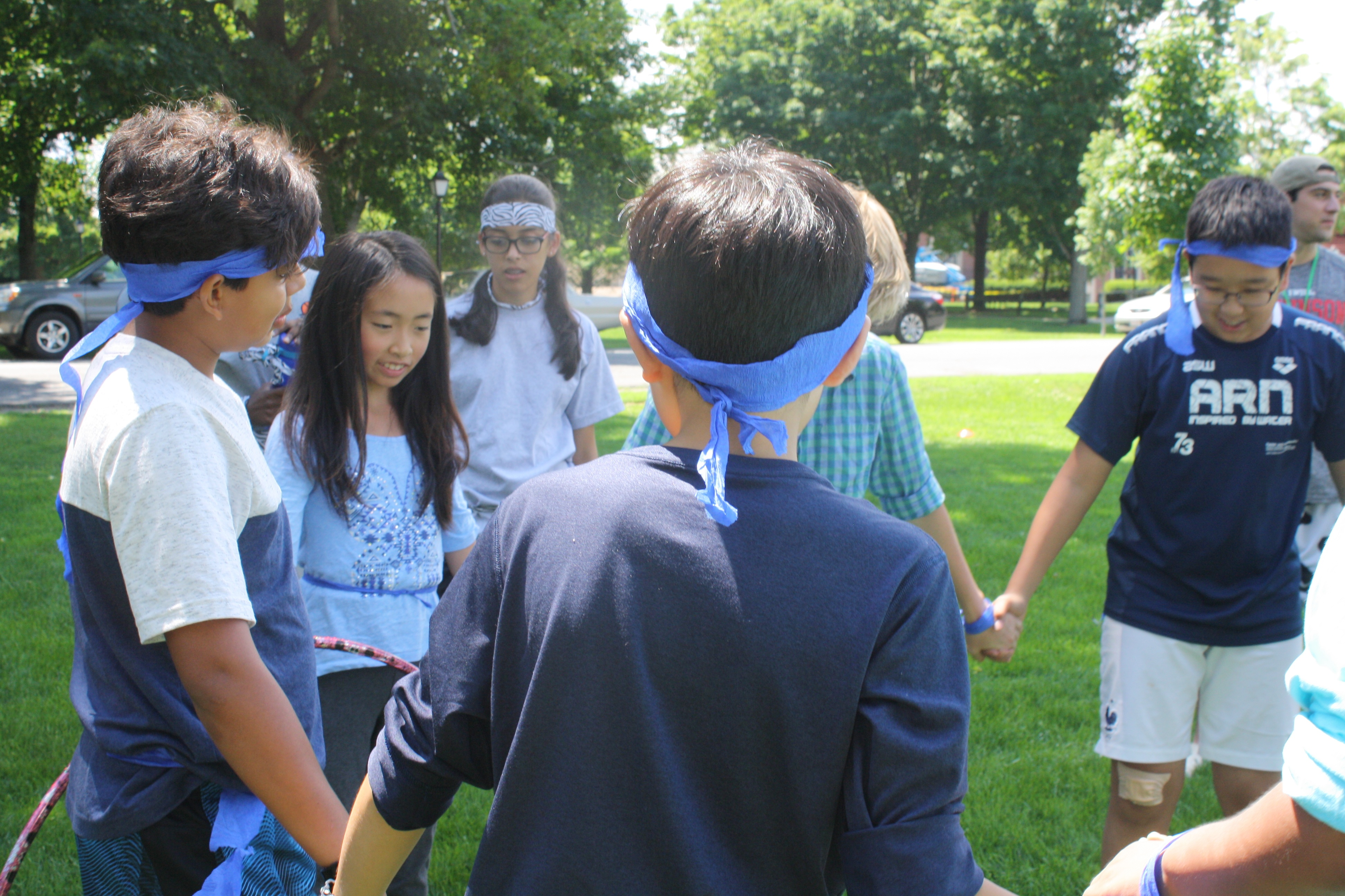 Midde school students from two summer programs play a hula hoop challenge