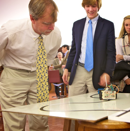 Mr. Bakker watches a student's robot perform its assigned task
