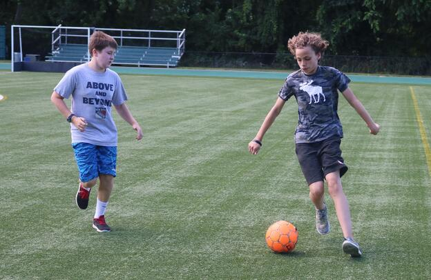 Two eighth grade boys play soccer during the afternoon co-curricular time.