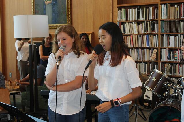 A student band sings for family and faculty in the library