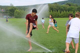 Middle school students play in sprinklers during Exp15