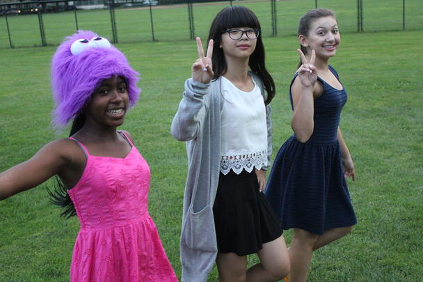 Three eighth grade girls being their fun selves on their way across campus.