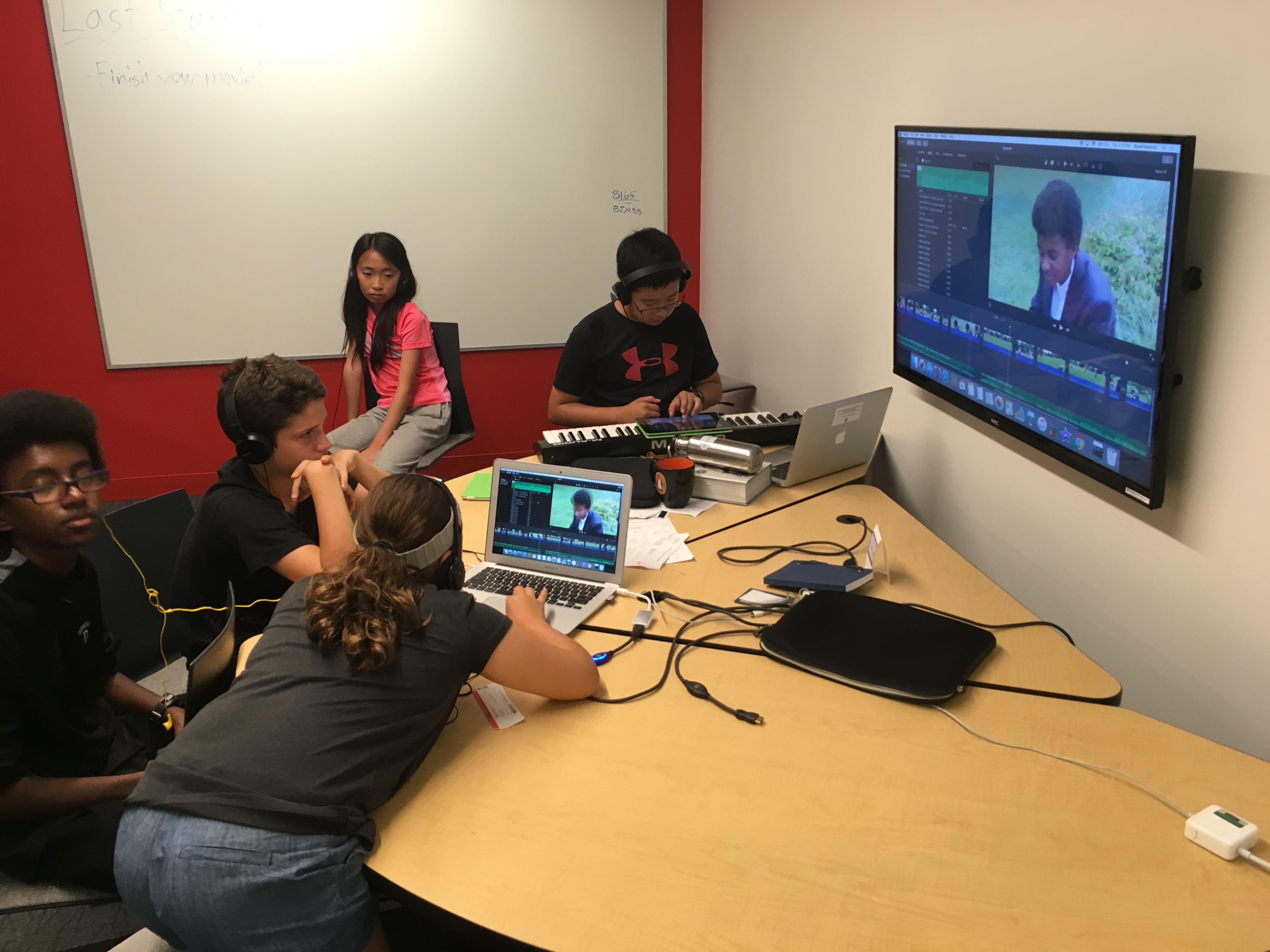 A group of students edit their film while Shawn composes some additional music for the score.