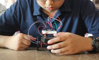 A seventh grader wiring a robot