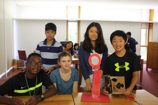 Students from around the world stand proudly around the tech project they built together.