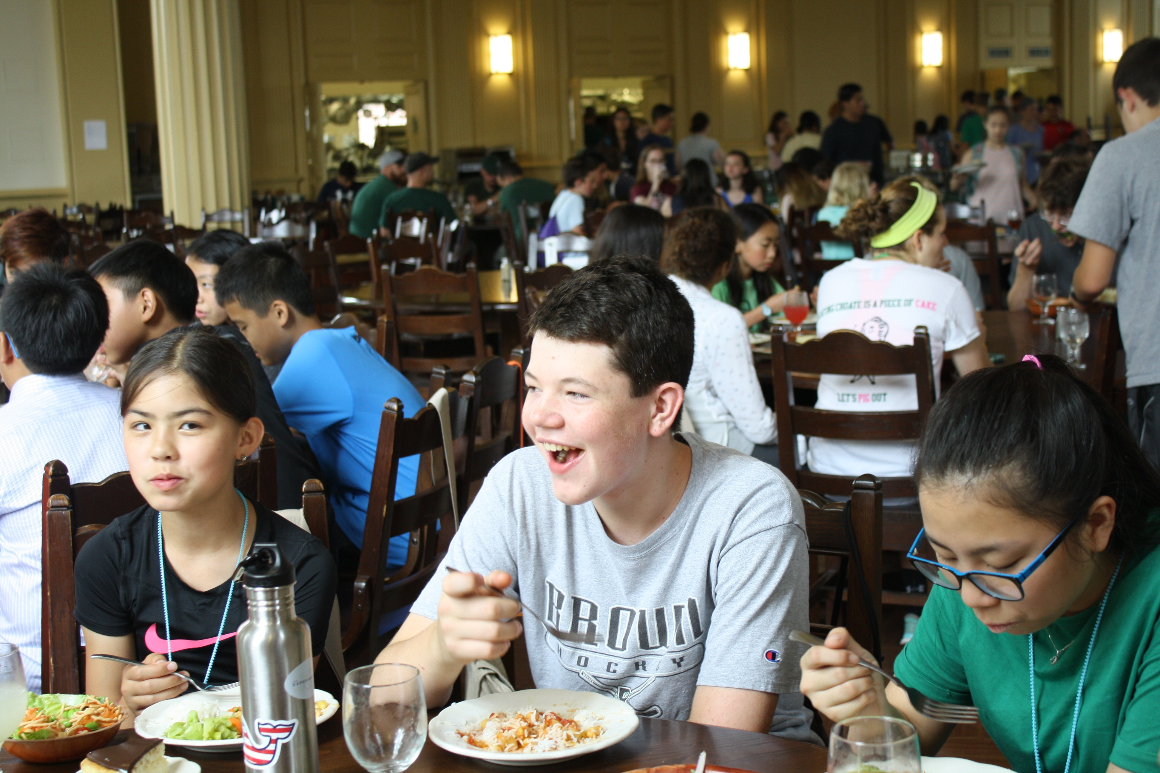 Students laughing over lunch in the dining hall.