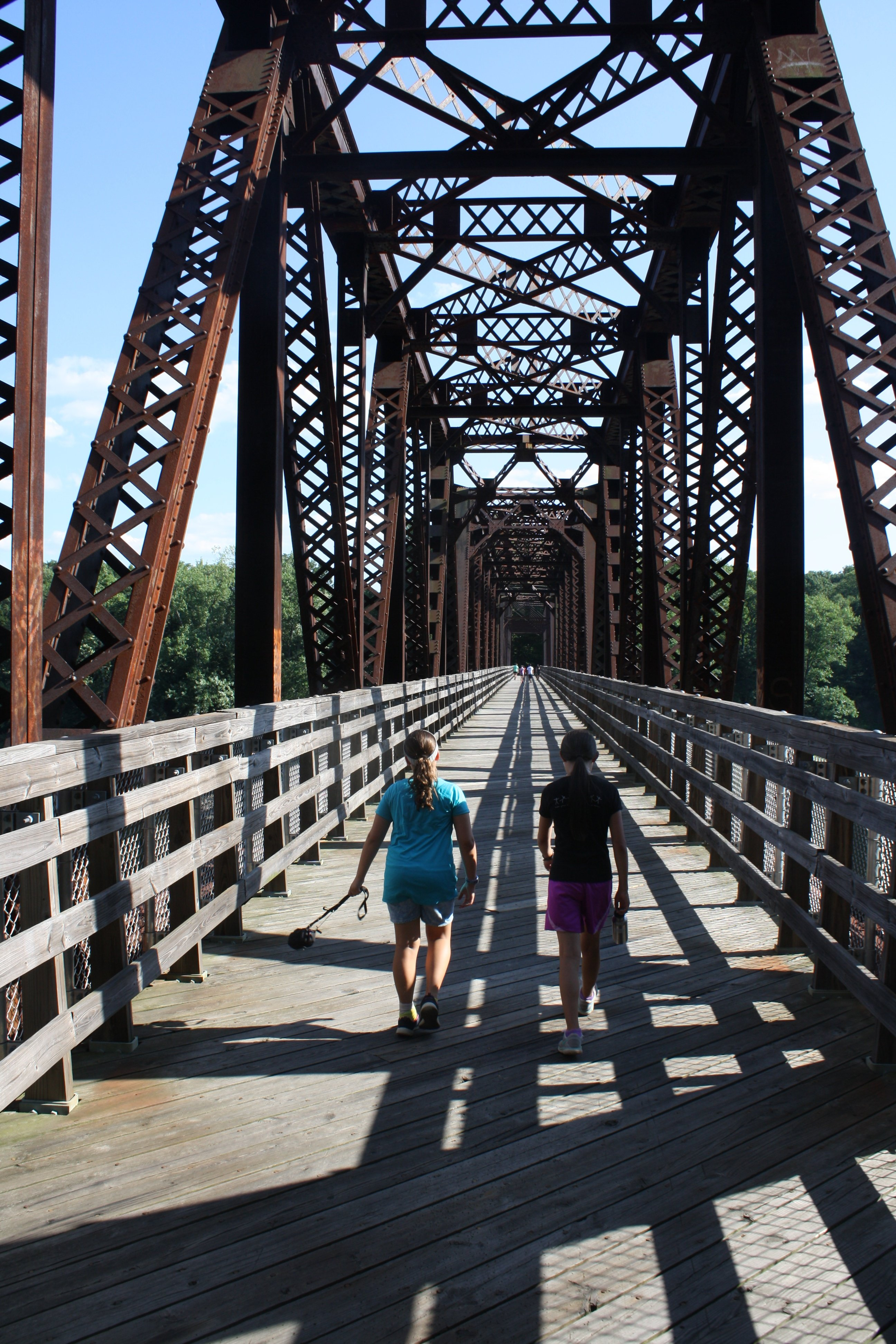 Bella and Lucy cross a walking bridge during a hiking cocurricular.