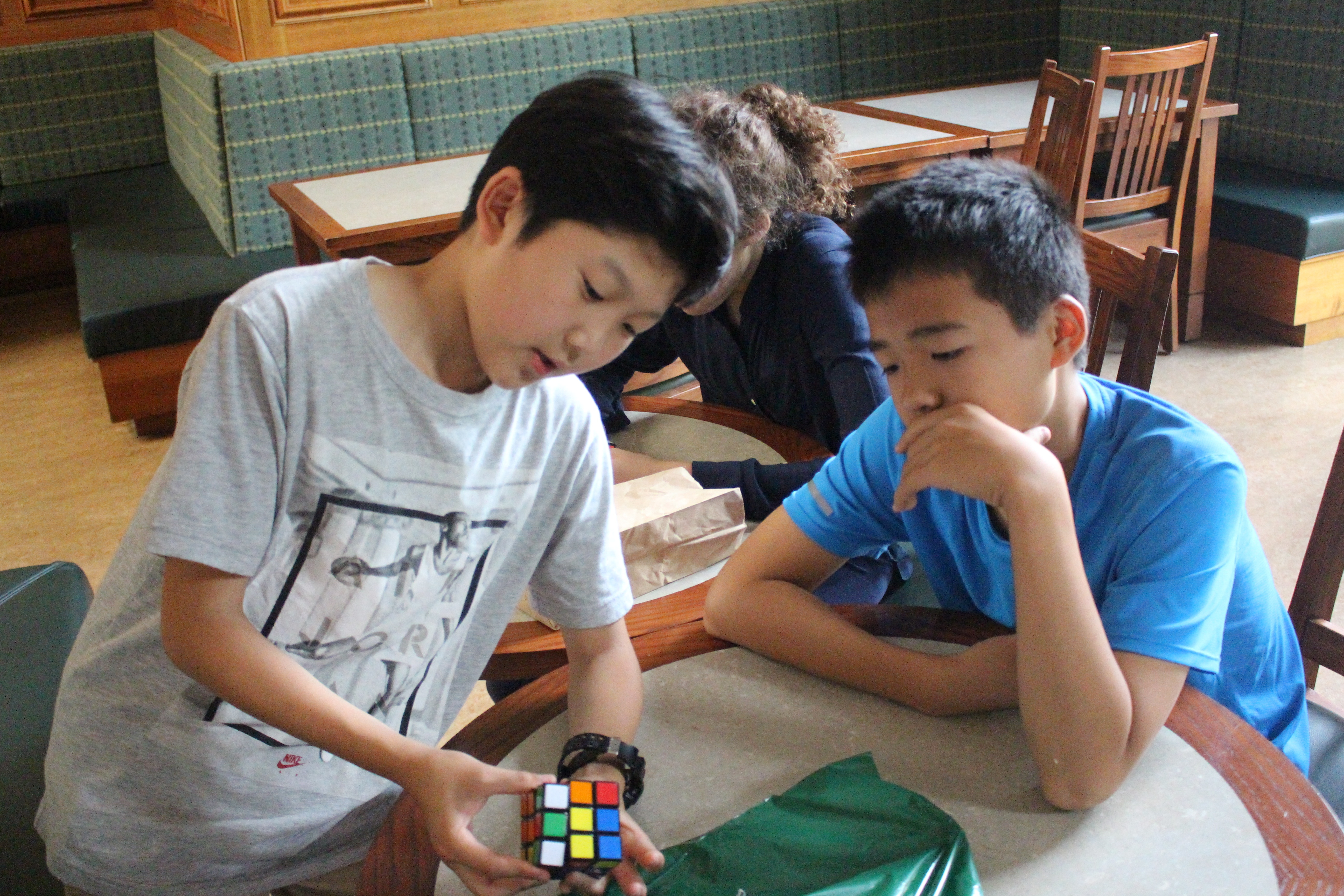 Two seventh graders confer over Rubiks Cube strategy