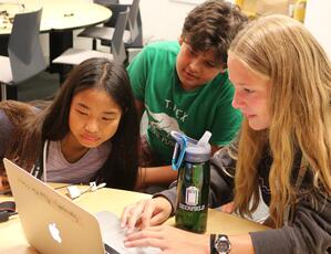 Three students gather around a laptop to collaborate on their film project.