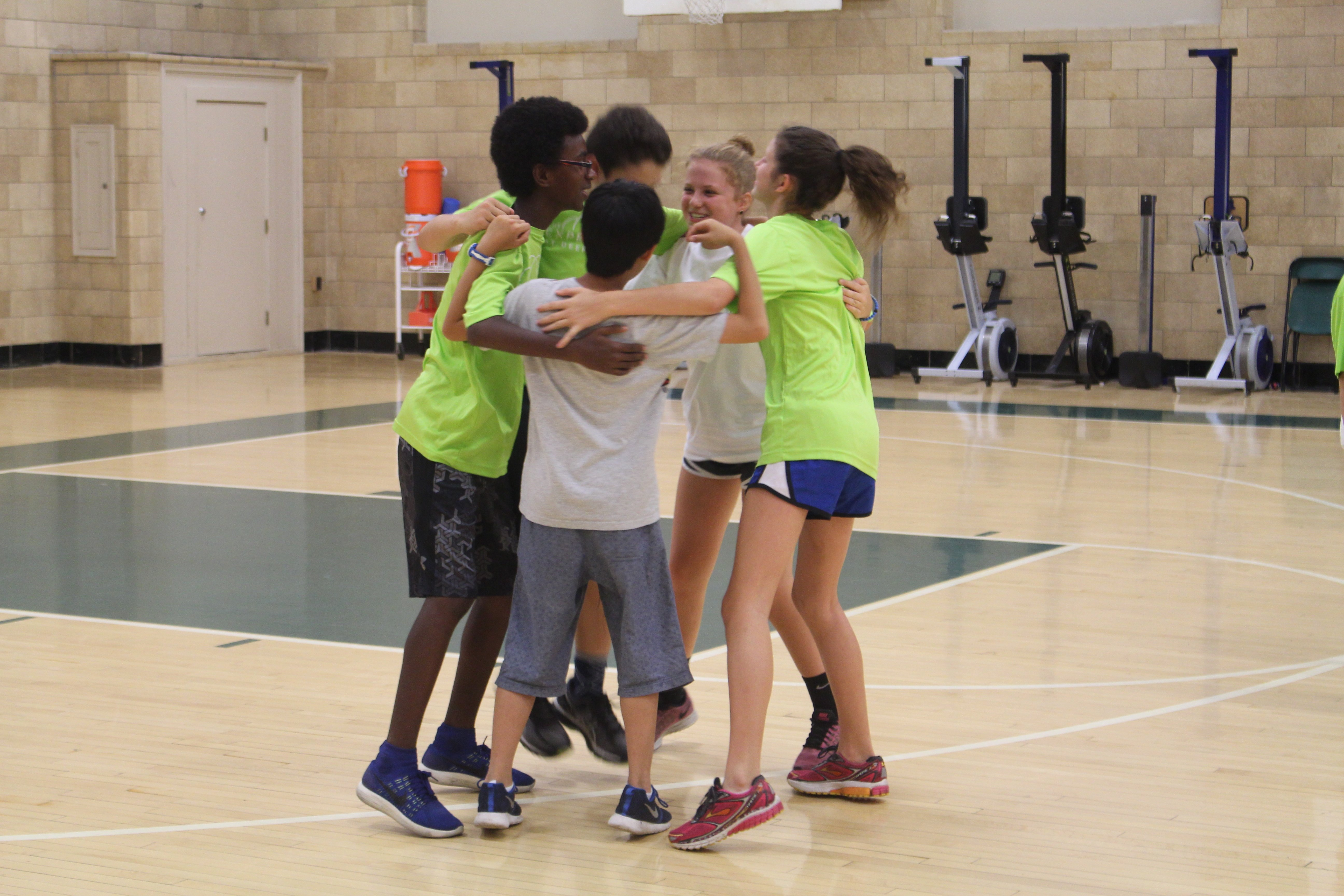 Students huddle for team spirit in our Olympic Basketball playoffs.