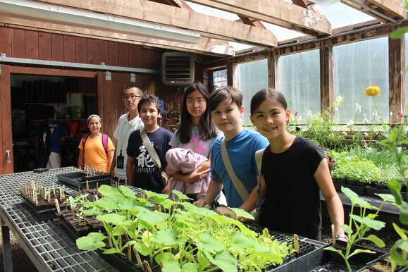 Six middle school students stand proudly over plants they tended while learning about sustainable agriculture.