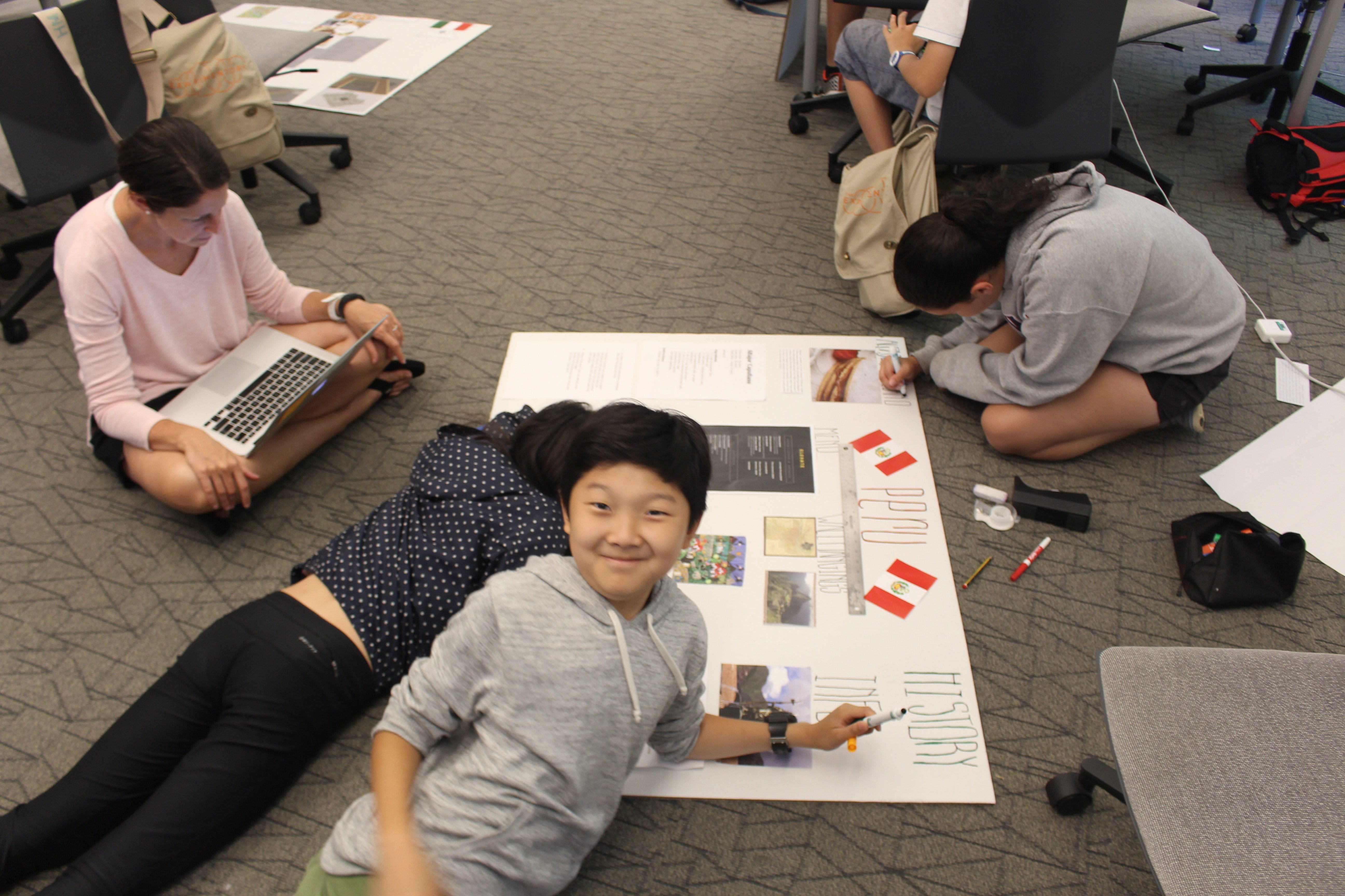 Students add architectural drawings and cultural information to their presentation boards.