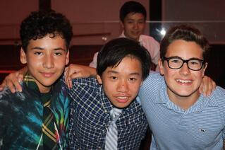 Three eighth grade boys hanging at the Experimentory dance
