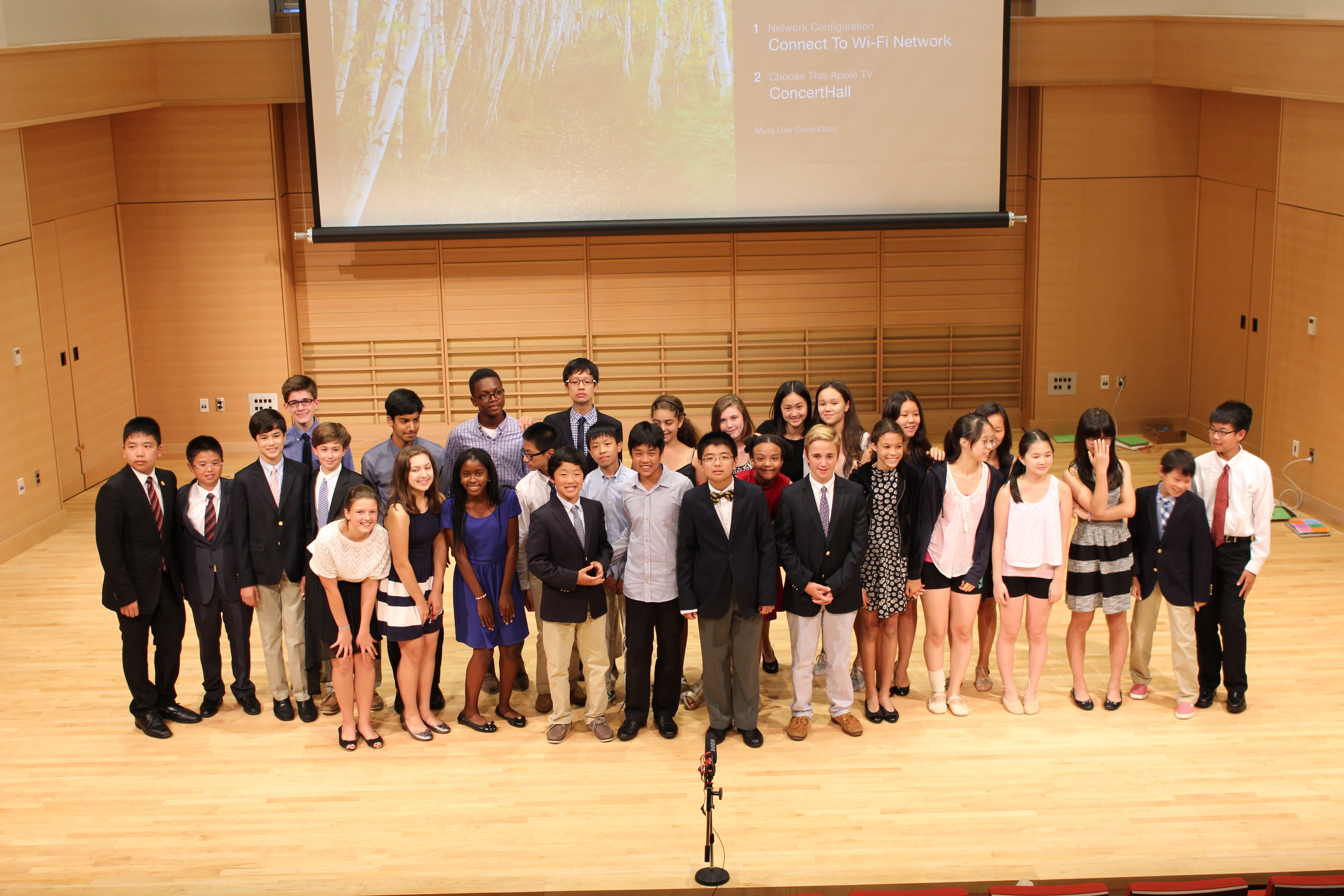Seventh and eighth graders stand for one last picture on stage during their final presentations.