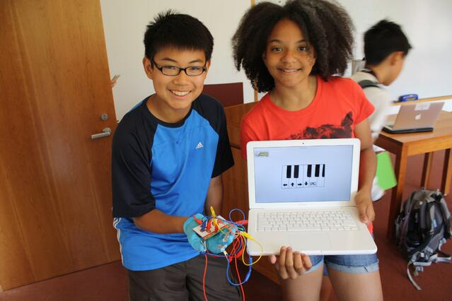 Two middle school students show off a prototype of their creative, collaborative summer project